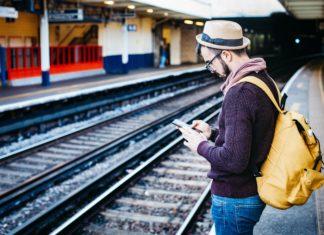 Ein Mann mit Hut steht auf einem Bahnsteig, er blickt auf sein Smartphone