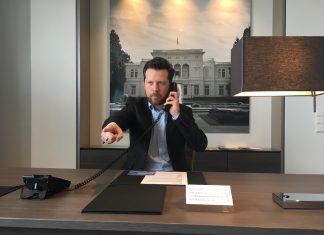 Johannes sitzt mit Jacket und Hemd an einem Schreibtisch, hat einen Telefonhörer in der Hand und zeigt mit dem anderen in das Bild, Boss-Style.