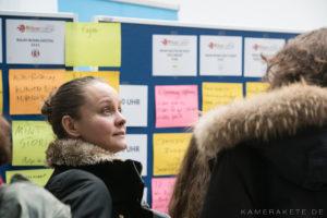 Eine Frau steht vor zwei Metaplanwänden, auf denen bunte Zettel kleben. Sie schaut von den Metaplanwänden weg zu einer anderen Person, die nicht im Bild ist.
