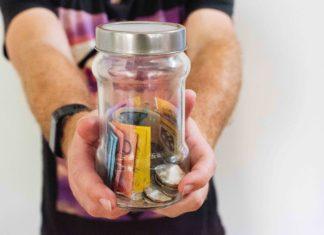 Ein Mann hält ein großes Einmachglas in der Hand, das mit Geldscheinen und Münzen gefüllt ist.